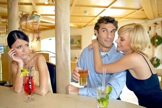 Stock Photo: 4292-131185 Mann flirtet mit zwei Frauen an der Hotelbar Eifersucht, Man flirting with two women at a hotel bar jealousy
