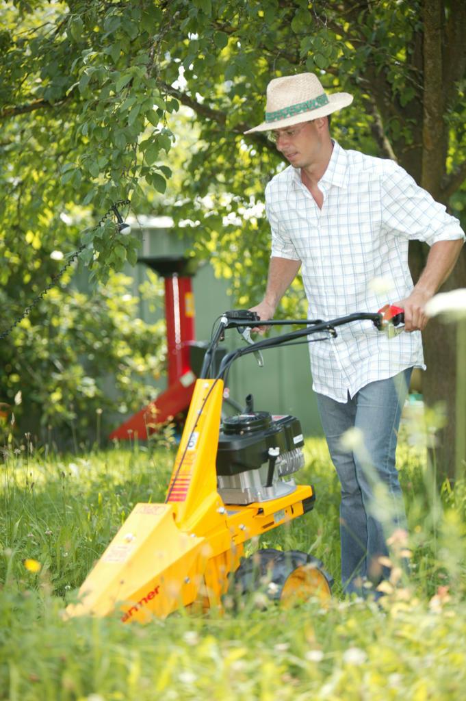 Stock Photo: 4292-131190 Mann maeht das Gras in seinem Garten mit einem Balkenmaeher