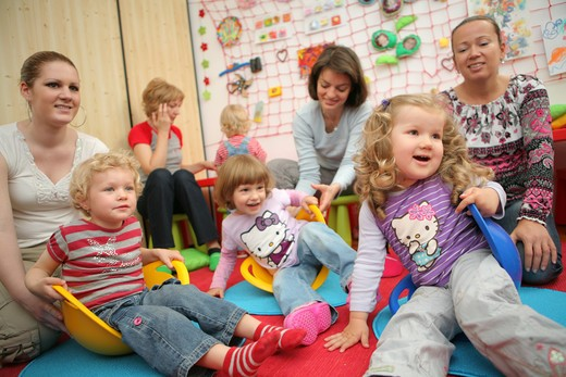 Kindergarden, mothers, women with playing children : Stock Photo