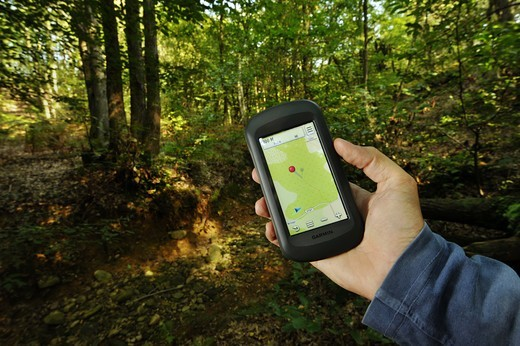 Stock Photo: 4292-139043 Man holding gps unit in forest