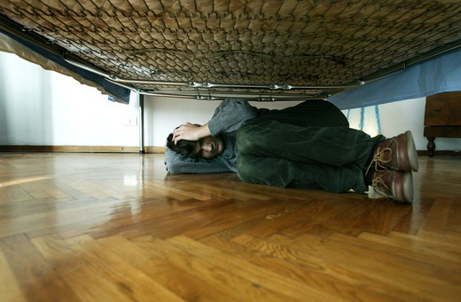 Stock Photo: 4292-13936 Depressed boy under the bed