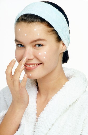 Woman spreading cream on her face : Stock Photo