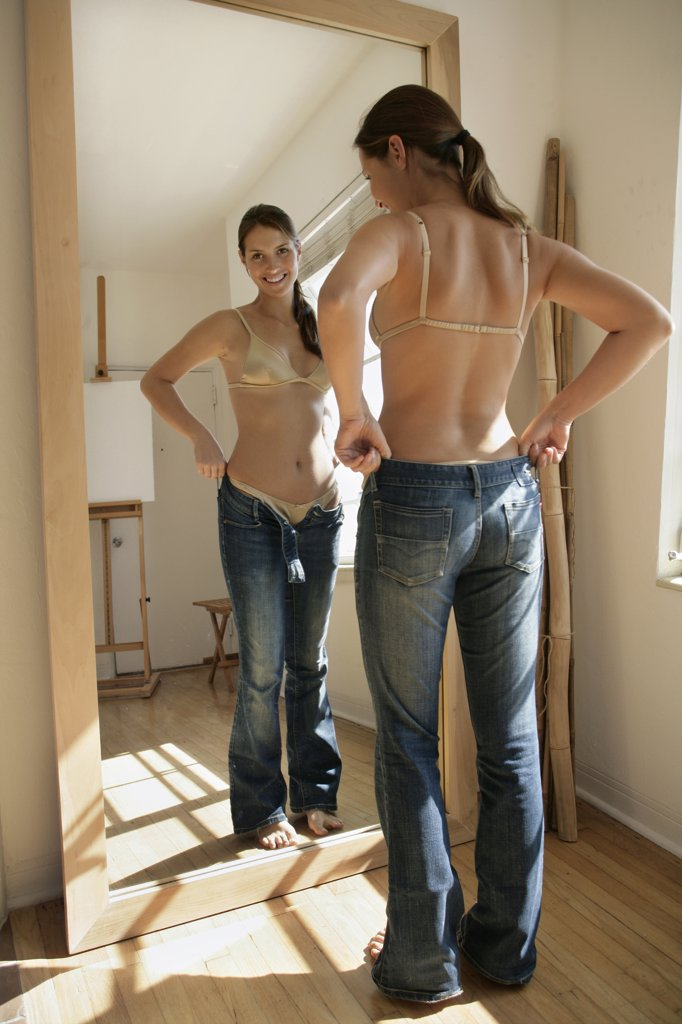 Stock Photo: 4292-14467 Woman in front of mirror trying on jeans