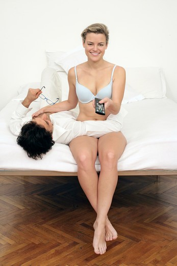 Couple on bed, woman with remote control : Stock Photo