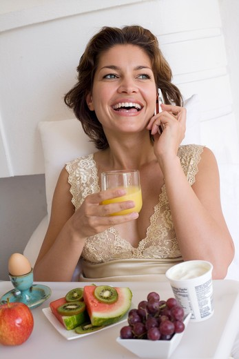 Woman having breakfast in her bed and talking on mobile : Stock Photo