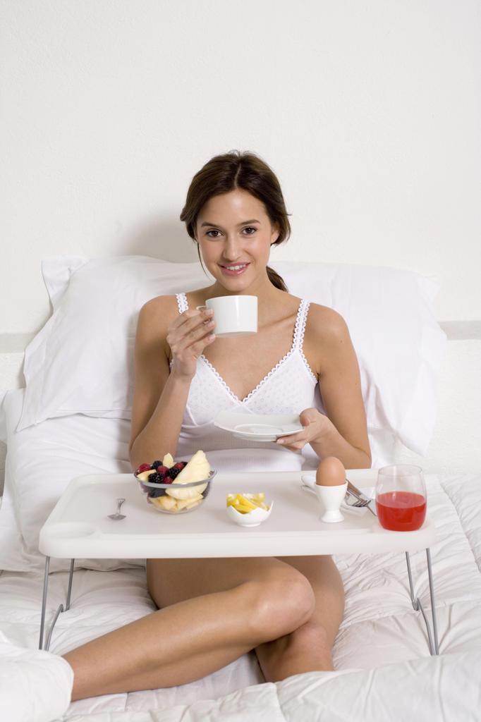 Woman having breakfast in her bed : Stock Photo