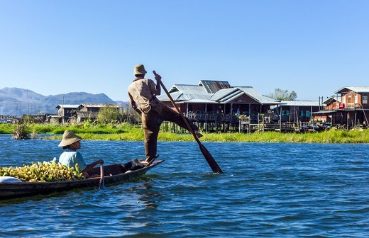Stock Photo: 4292-153137 Myanmar, Shan State, a boat coming from the market with the rower performing a typical way to row on the Inla Lake.