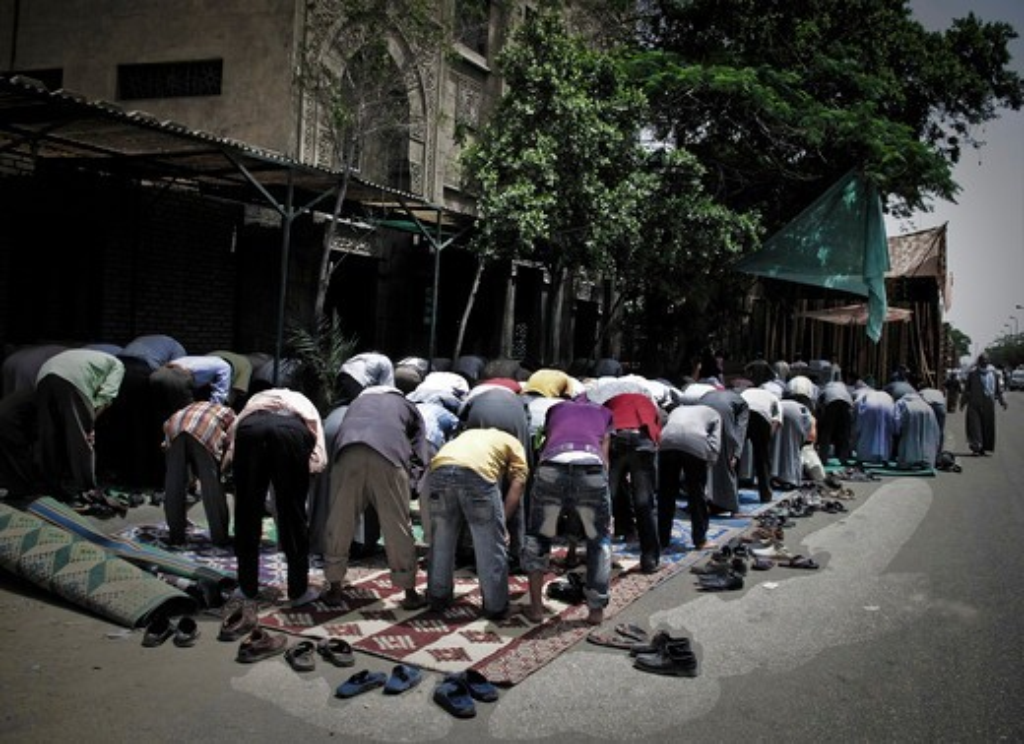 Egypt, Cairo, Market of El Mokatan close Muqattan Hill. Men in preyer on the road. : Stock Photo