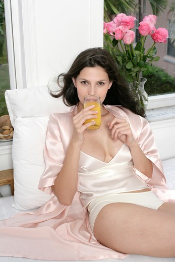 Portrait of young woman in underwear sitting on bed with glass of orange juice : Stock Photo