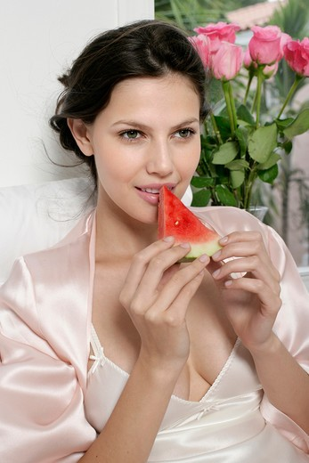 Young woman eating a slice of watermelon : Stock Photo