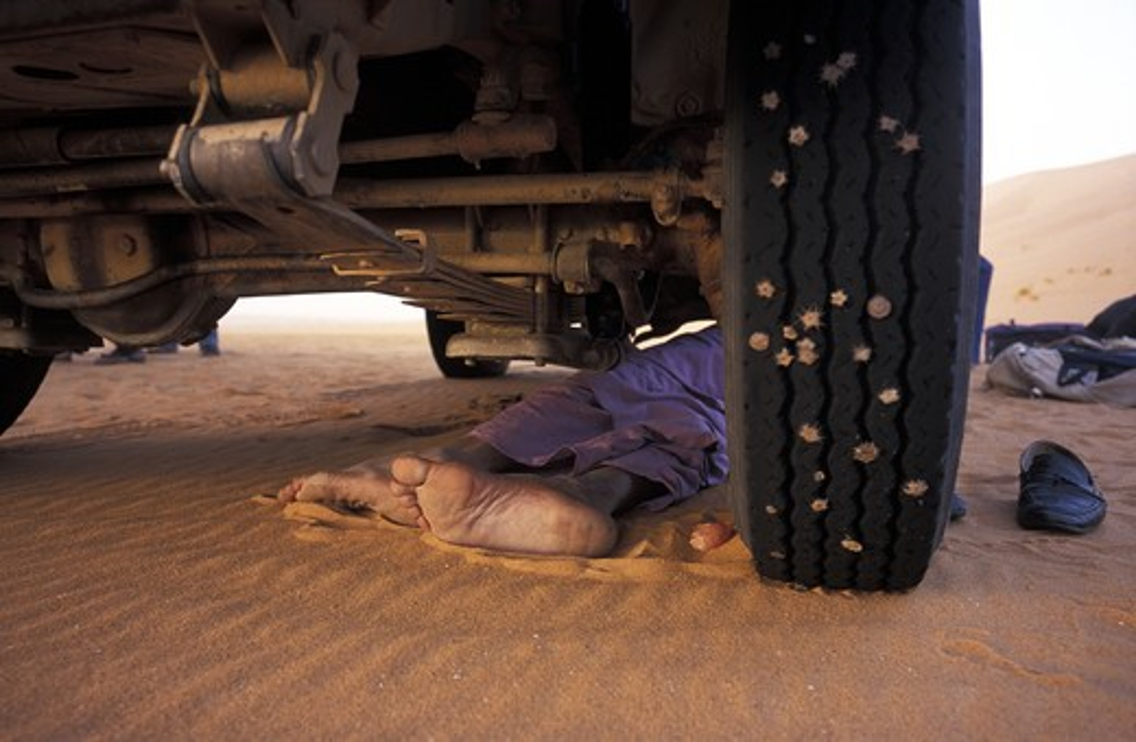 Stock Photo: 4292-16640 Algeria, Sahara, Erg Chech Desert, feet of a person lying under a car in the desert