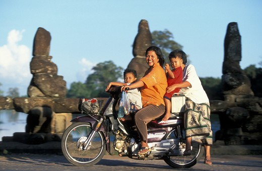 Stock Photo: 4292-31469 Cambodians on motorcycle in front of old statues of a temple