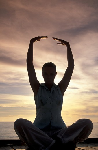 Stock Photo: 4292-31878 Maldives. Ari Atoll. White Sands Island and Resort. Woman practising yoga on the beach at sunset