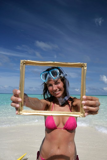 Stock Photo: 4292-35303 Woman's portrait at sea holding an empty frame