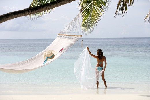 Stock Photo: 4292-35543 Woman with pareu standing by hammock