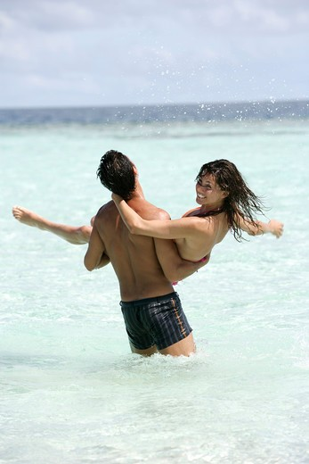 Couple at sea playing in shallow water : Stock Photo
