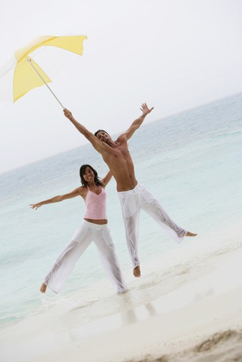 Playful couple standing on the beach : Stock Photo