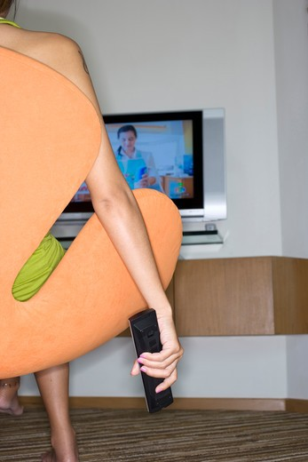 Stock Photo: 4292-36541 Woman sitting in arm chair, channel surfing