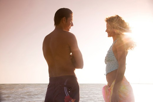 Couple standing on beach, rear view : Stock Photo