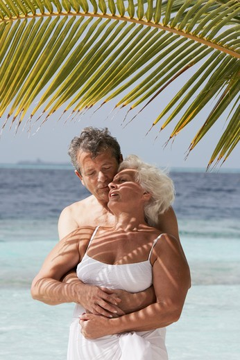 Stock Photo: 4292-37690 Maldives, Ari Atoll, senior couple embracing on the beach