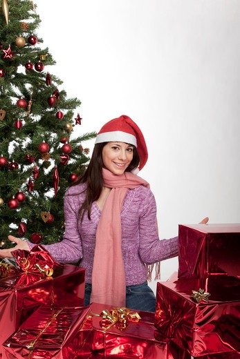 Stock Photo: 4292-38646 Portrait of woman standing by christmas tree and gifts