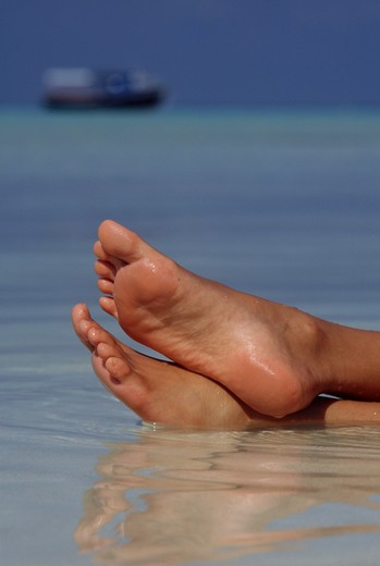 Maldives, Feet of a woman relaxing in the water : Stock Photo