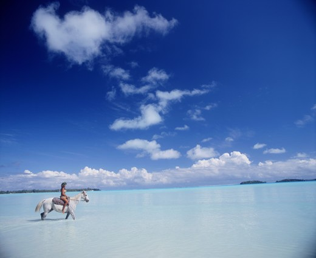 Stock Photo: 4292-40821 French Polynesia, Bora Bora, local girl riding horse in the lagoon