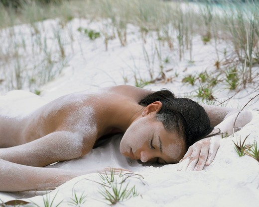 Woman lying on the beach : Stock Photo
