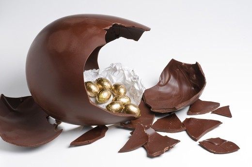 Broken Easter chocolate egg with golden eggs surprise : Stock Photo