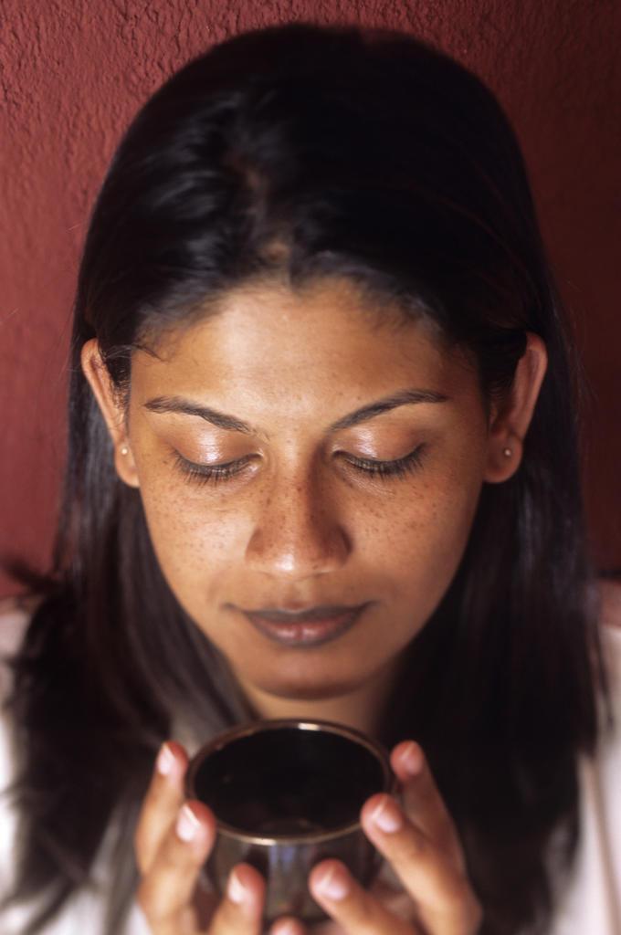 Mauritius Island, Young woman having a coup of tea : Stock Photo