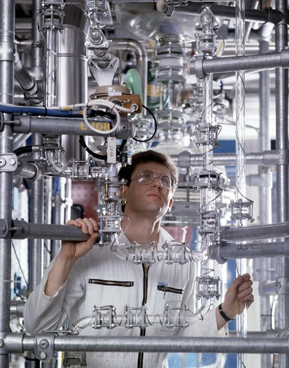 Engineer checking distilling apparatus in alcohol manufacturing : Stock Photo