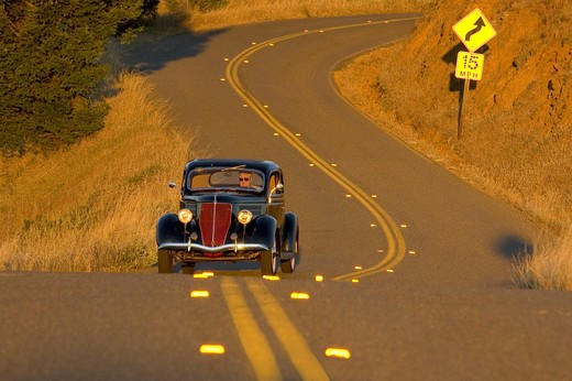 Automobile 1936 Ford coupe on winding road in Northern California : Stock Photo