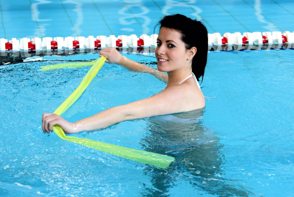 Stock Photo: 4292-59600 Woman in swimming pool doing pilates exercise