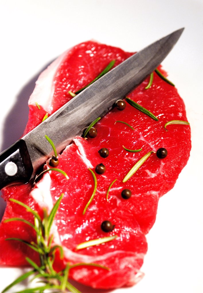 Raw beef steak with rosemary and peppercorns : Stock Photo