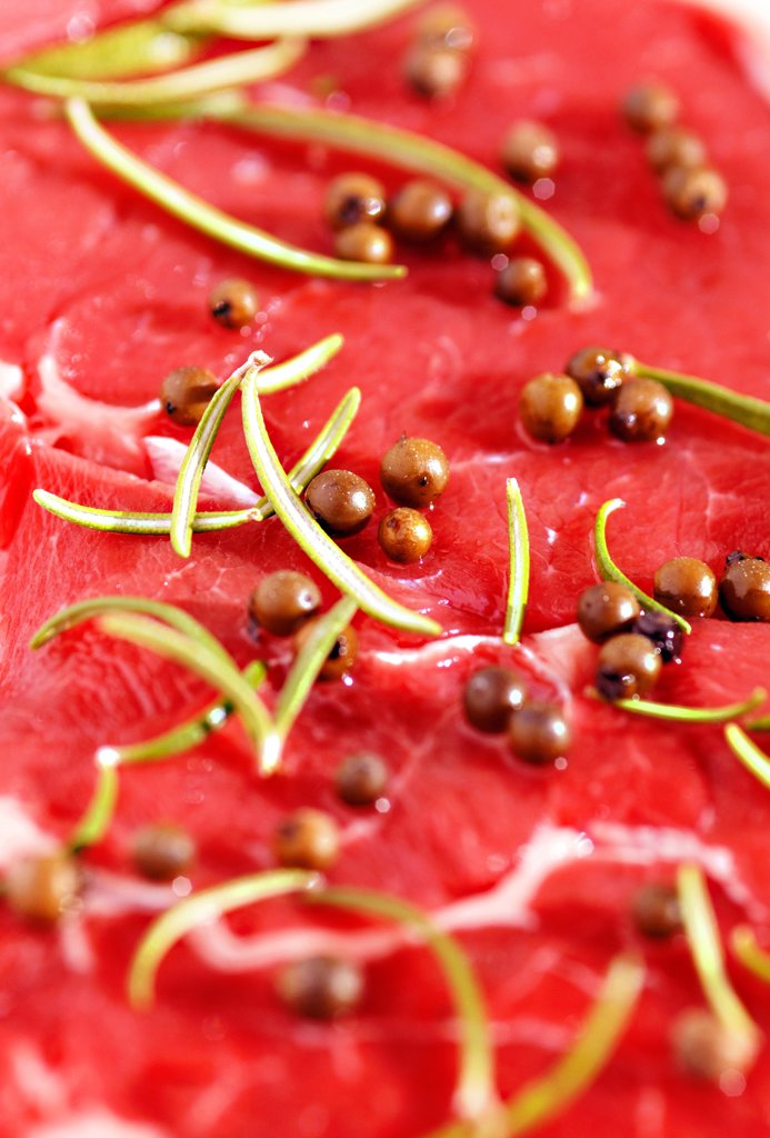 Stock Photo: 4292-63028 Raw beef steak with rosemary and peppercorns