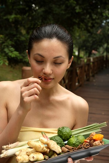 Girl holding a tray full of ingredients for Jamu - Indonesian Herbal Elixir : Stock Photo