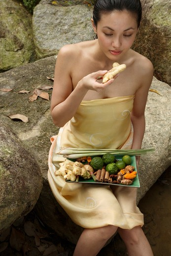 Stock Photo: 4292-6615 Girl holding a tray full of ingredients for Jamu - Indonesian Herbal Elixir