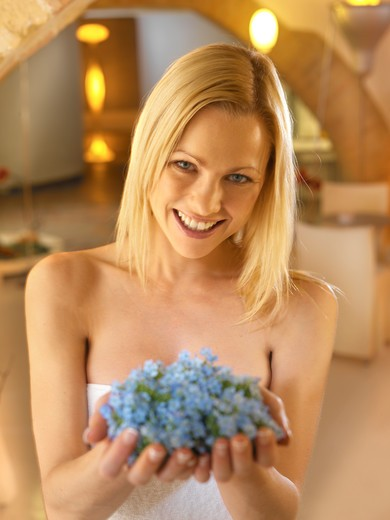 Portrait of woman holding myosotis flowers : Stock Photo