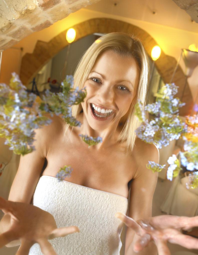 Stock Photo: 4292-66517 Woman throwing myosotis flower in air