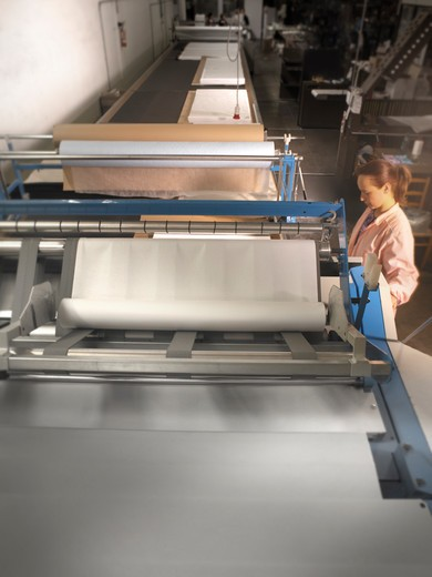 Young woman working in textile factory (No Property Release!) : Stock Photo