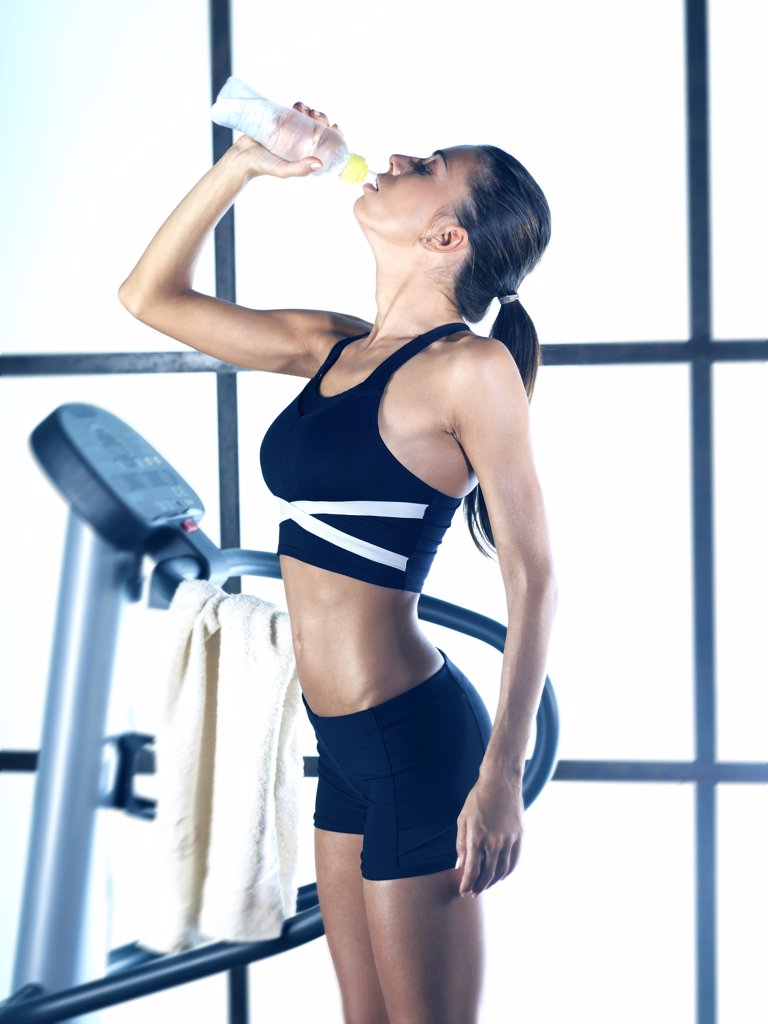 Stock Photo: 4292-67141 Young woman in fitness room drinking water from a bottle