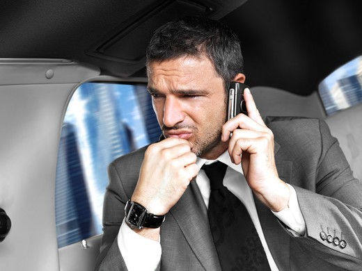 Businessman on mobile sitting in the back seat of a limousine : Stock Photo