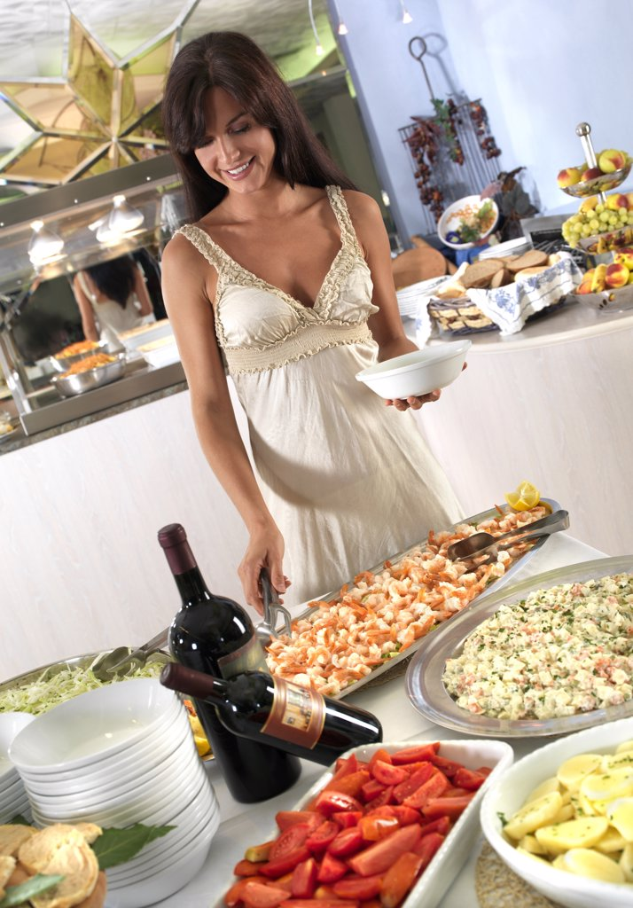 Stock Photo: 4292-68147 Woman standing in front of a buffet