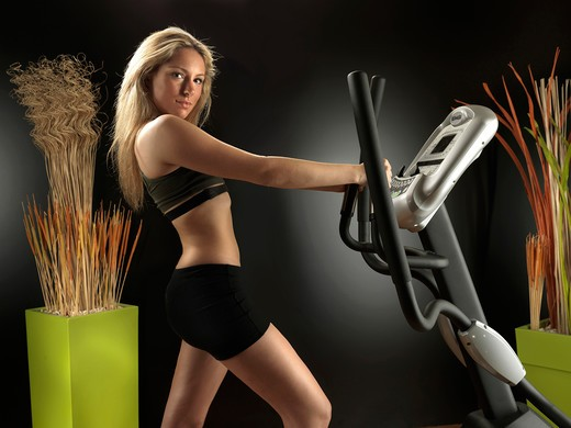 Woman at gym on exercise machine : Stock Photo