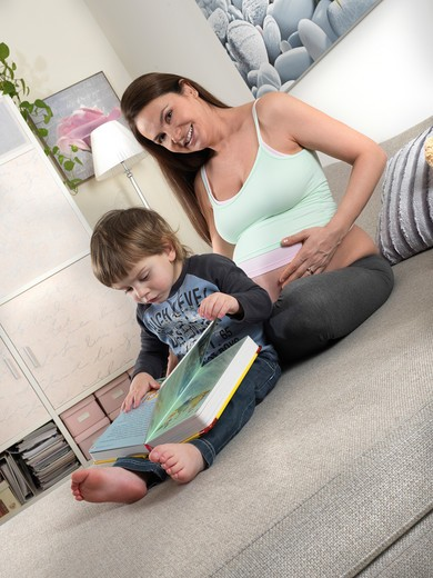 Stock Photo: 4292-68583 Pregnant mother reading a book with son