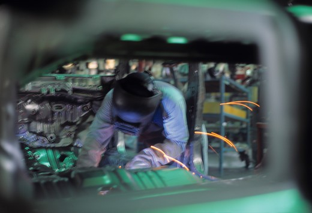 Welder in car factory : Stock Photo