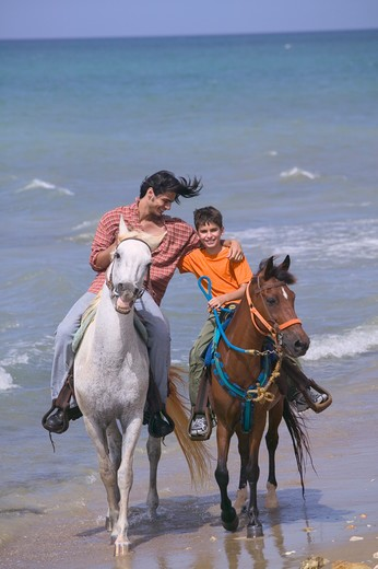 Father and son horseback riding on beach : Stock Photo
