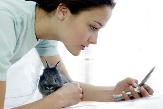 Stock Photo: 4292-73802 Woman sending a message and holding a rabbit