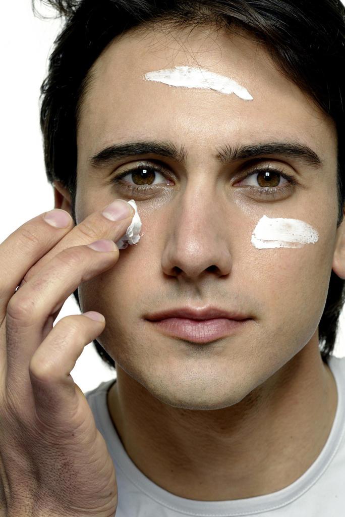 Man spreading cream on his face : Stock Photo