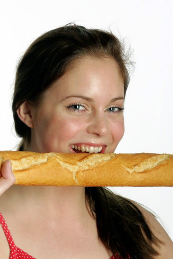 Younf woman biting a baguette : Stock Photo